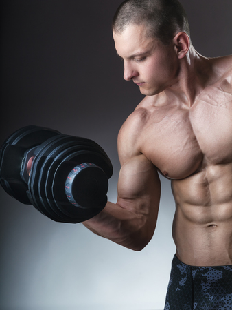 Fit muscular man exercising with dumbbell on dark background Standard-Bild - 120934681