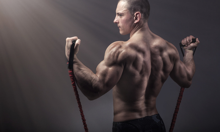 Sports concept. Athletic young man exercising with rubber band against a dark background Stock Photo