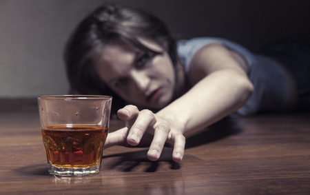Depressed young woman drinking alcohol while lying on the floor