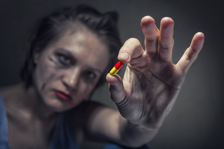Young woman holding a pill addict. Focus on hands Standard-Bild - 120934786