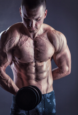 Fit muscular man exercising with dumbbell on dark background Stock Photo