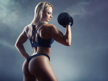 Sport concept. Athletic young woman exercising with heavy weights against a dark background. Back view