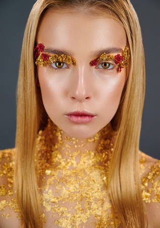 Gilded body. Golden makeup. Portrait of a young woman with makeup fashion. The neck is covered with gold glitter Standard-Bild - 123219276
