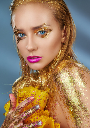 Portrait of a beautiful woman with sparkles on her face and body. Fashion model with golden makeup and yellow tulips