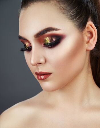 Close up of fashion model young woman in trendy make-up. Eye models with colorful glitter on the eyelids. The gaze of the girl is directed downwards Standard-Bild - 125853502