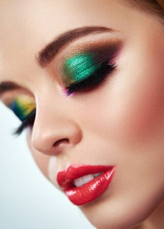 Close up of fashion model young woman in trendy make-up. Eye models with colorful glitter on the eyelids Standard-Bild - 125853505