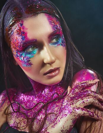 Portrait of a beautiful fashion model woman with sparkles on her face and body
