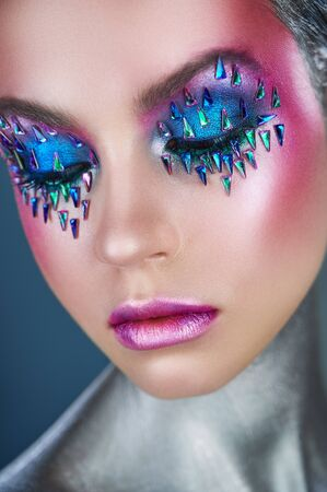 Close-up of fashion model woman with trendy metallic make-up. High fashion model. Glitter vivid makeup. Fashion makeup