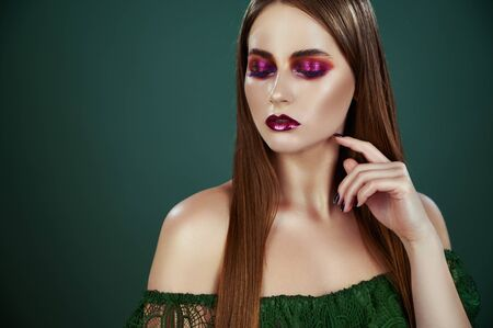 Evening makeup. Portrait of young beautiful woman with long hair and bright evening makeup on emerald background Standard-Bild - 125853747