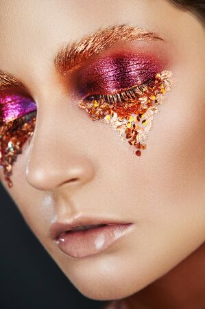 Closeup portrait of a girl of fashion model in art fashion golden make-up. Eye models with colorful glitter on the eyelids.