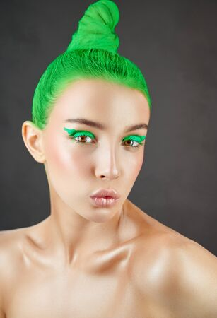 High fashion model. Amazing woman with green hair and arrows on her eyes