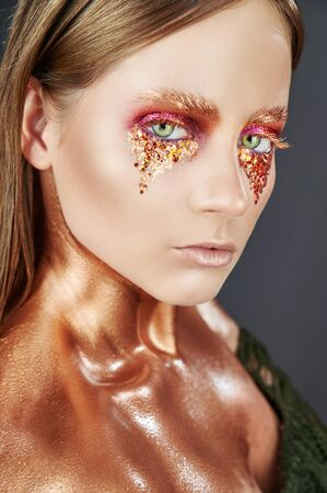 Gilded body. Golden makeup. Woman with golden makeup and body art. High fashion model