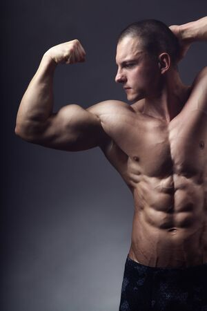 Bodybuilding. Handsome sports man posing in front of the camera on a black background. Shows his pumped-up torso and hands 写真素材