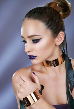 Close-up portrait of young woman with smokey eyes and accessories with collar and bracelet. Modern fashion rock makeup Standard-Bild