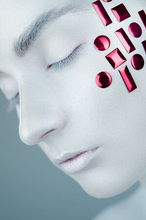 High fashion model. Girl in white makeup and accessories with eyes closed. White skin make-up. Art design makeup