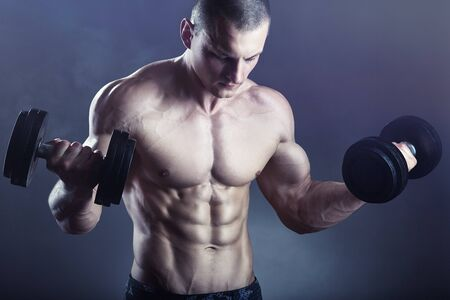Handsome young muscular man exercising with dumbbell on dark background