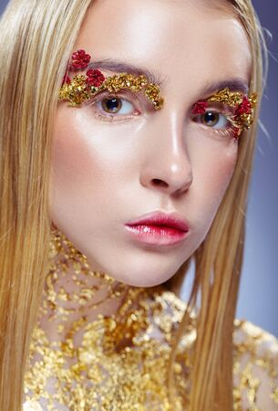Gilded body. Golden makeup. Portrait of a young woman with makeup fashion. The neck is covered with gold glitter