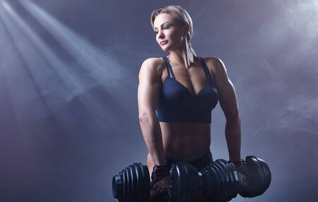 Fitness young woman with heavy weights on a dark background. Sport concept Standard-Bild