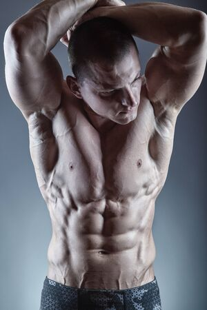 Close-up of a young athlete showing his sporty torso against a dark background