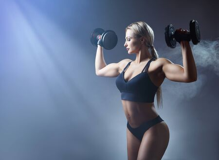 Beautiful sporty woman with heavy weights against a grey background. Sport concept