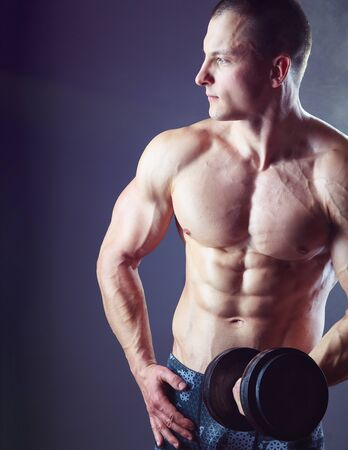 Fit muscular man exercising with dumbbell on dark background Standard-Bild