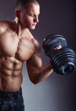 Bodybuilder. Fit muscular bodybuilder man exercising with dumbbell