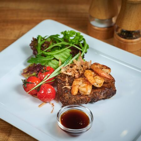 Dish of meat on a plate adding with shrimp, tomatoes and salad. Grilling steak
