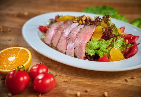 Plate with mouthwatering gourmet dish with roasted duck breast and salad with vegetable Reklamní fotografie