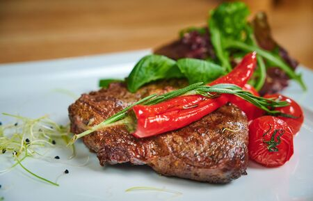 Juicy steak. Dish of meat on a plate adding with shrimps, tomatoes and salad