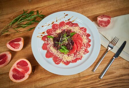 Beef carpaccio with grapefruit and lettuce. Arrangement with cutlery