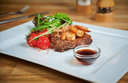 Grilling steak. Dish of meat on a plate adding with shrimp, tomatoes and salad Reklamní fotografie