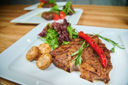 Restaurant dishes. Grilling steaks. Dish of meat on a plate adding with mushrooms, salad and red pepper