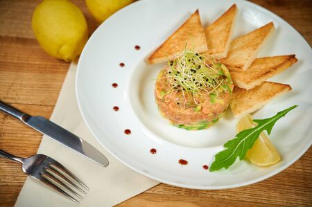 Delicious salmon tartare with avocado. Arrangement with a glass of wine and cutlery Reklamní fotografie