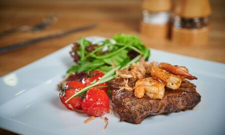 Grilling steak. Dish of meat on a plate adding with shrimp, tomatoes and salad. Arrangement with cutlery
