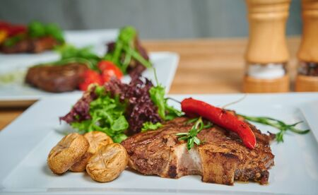 Grilling steak. Dish of meat on a plate adding with mushrooms, salad and red pepper