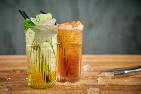 Two glasses with refreshing drinks. Delicious refreshing waters with cucumber and cinnamon in glasses Standard-Bild