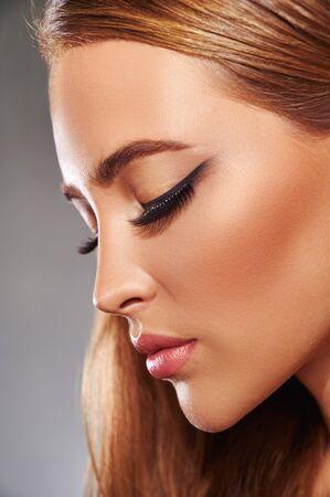 Beautiful fashion luxury makeup, false long eyelashes, perfect skin facial make-up. Side view Standard-Bild
