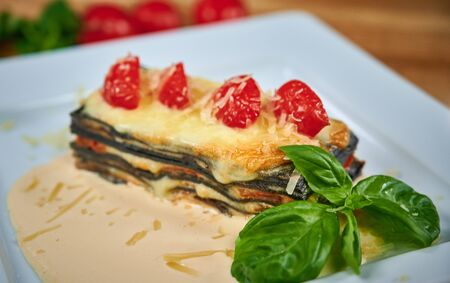 Italian black lasagna with salmon and mushrooms serving on white plate in restaurant