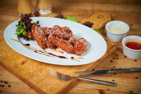 Serving of delicious spicy chicken wings with sesame seeds and sweet chili sauce on white wooden board Standard-Bild