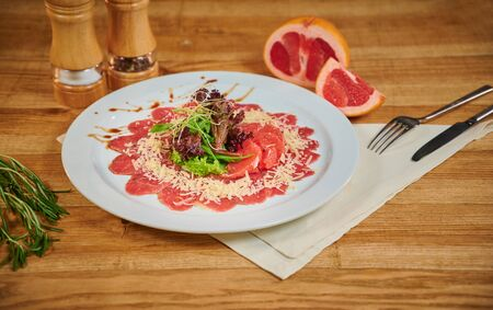 Close up of a beef carpaccio with grapefruit and lettuce in a restaurant Reklamní fotografie