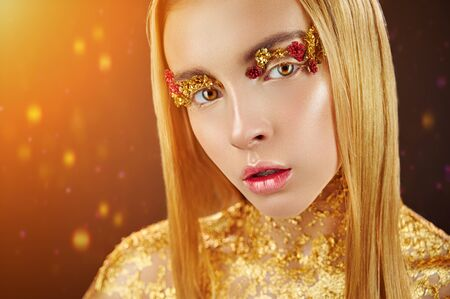 Golden makeup. Portrait of a young woman with makeup fashion. The neck is covered with gold glitter