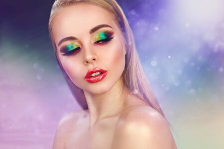 Cute blonde fashion model girl in trendy make-up. Eye models with colorful glitter on the eyelids