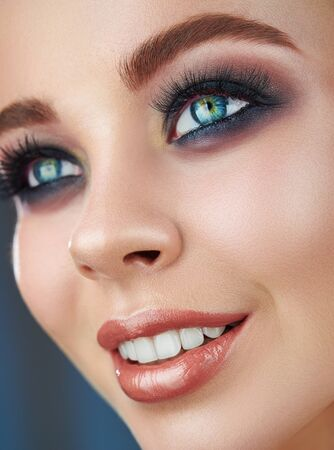 Close-up of a beautiful young smiling woman with trendy natural makeup