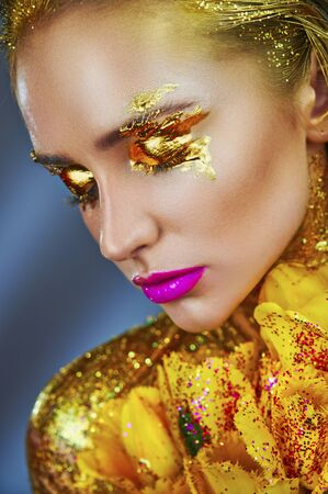 Portrait of a beautiful woman with sparkles on her face and body.