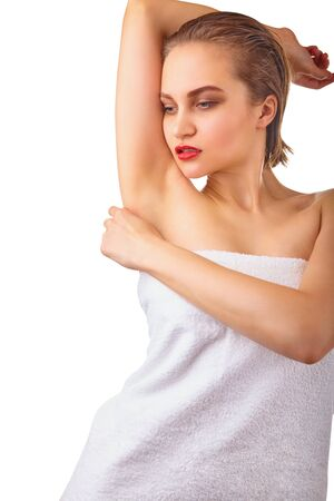 Close-up of a beautiful young woman in towel shows armpit on a white