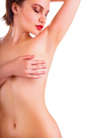 Young woman looking at her clean armpit isolated on white