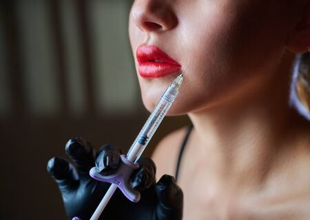 Cosmetology. Portrait of beautiful young woman face with syringe. Beauty treatment. Cosmetic or botox injections