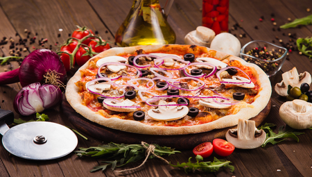 Italian pizza with mushrooms, olives and onion rings with ingredients on wooden table (close)