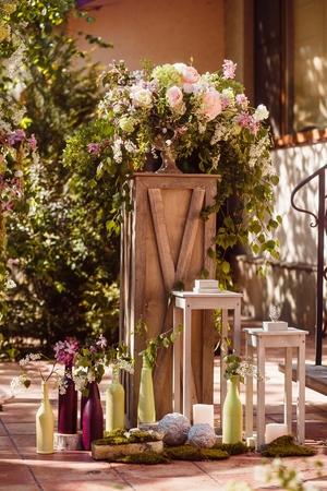 Wedding decoration ceremony. Fresh flowers in vases Фото со стока
