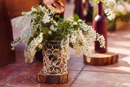 A bouquet of white lilac in a wrought-iron vase at a wedding ceremony Фото со стока